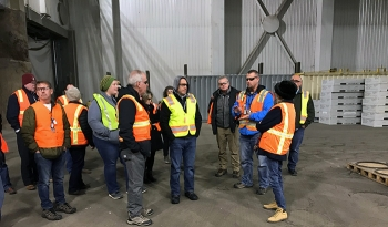 Nate Loftus with Fluor Idaho, EM's Idaho National Laboratory Site contractor, addresses the EM Site-Specific Advisory Board Chairs inside the Transuranic Storage Area/Retrieval Enclosure, where thousands of waste drums await shipment to EM's Waste Isolati