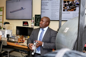 Florida International University DOE Fellow and doctorate student Mackenson Telusma discusses his robotic wall crawler for inspection of nuclear facilities during a tour of Florida International University's Applied Research Center.