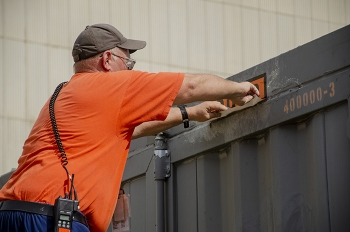 Damon Cates applies labels on a shipping container in preparation for the first cold trap leaving the EM Paducah Site.