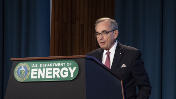 """Anthony Cancelosi speaks at a podium, the podium is branded """"US Department of Energy."""""""