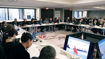 Large group of people seated around a room in a square-shaped configuration of tables, at IFNEC Week 2019 in Washington, D.C.