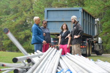 Daniel Ball, right, welding instructor at the Aiken County Career Center, examines the donated stainless steel with Tina Paschal, Nicole Henley and Rachel Baxley of SRNS.