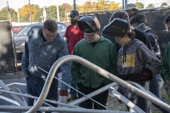 Michael Meyer, left, welding instructor at Evans High School, and welding students examine the donated stainless steel from SRS.