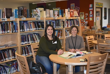 Volunteer Maribel Dominguez, left, and Communities In Schools New Mexico Site Coordinator Alex Mazares meet in the library to discuss the students with whom Dominguez will meet and provide learning assistance.