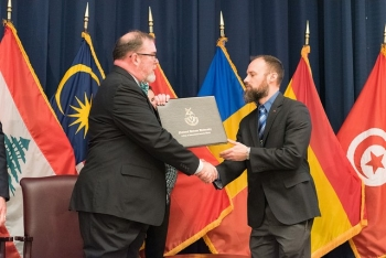 OST Federal Agent Chris Sterie receives a diploma from Dr. Charles B. Cushman, Chancellor, College of International Security Affairs.