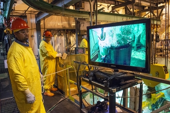 Savannah River Nuclear Solutions employees Erik Tucker, left, and Randy Fanning watch as the inner lid of a High Flux Isotope Reactor (HFIR) spent nuclear fuel shipping cask is removed under water in the L Area disassembly basin.