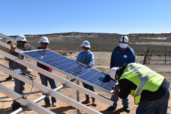 Trainees install a solar panel on a ground-mounted array at the Navajo Technical University in Ojo Encino, New Mexico.