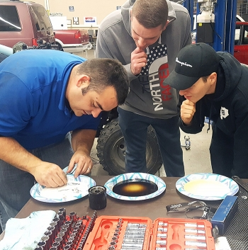 Steven Kirschenmann, left, a training specialist, demonstrates lubrication principles of oil-based lubricants to Columbia Basin College (CBC) students James Longmire, center, and Austin Silveira during a hydraulic and fluid flows class.