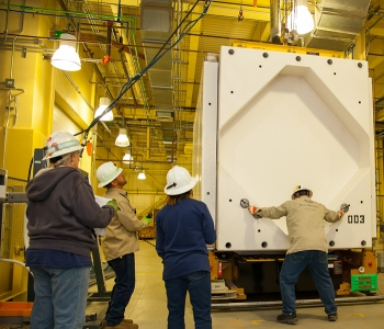 A worker removes the 6,000-pound cover of a Transuranic Package Transporter Model 3 cask during a practice session at the Waste Isolation Pilot Plant.
