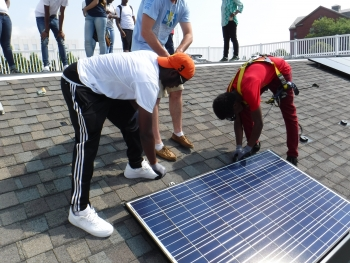 High school students practice installing solar panels on a mock roof