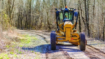 Heavy Equipment Operator Jeff Walls grades one of the 32 miles of roads maintained by Swift & Staley Inc. at the Paducah Site.