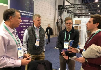 Deputy Under Secretary for Artificial Intelligence and Technology Dimitri Kusnezov and Senior Advisor Dan Wilmot talk with two of the many visitors to the AITO booth at CES 2020.