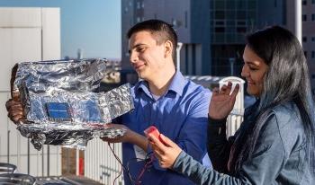 Sean Regalado-Love and Melissa Perez test their team's parabolic collector outside of NREL's Solar Energy Research Facility.