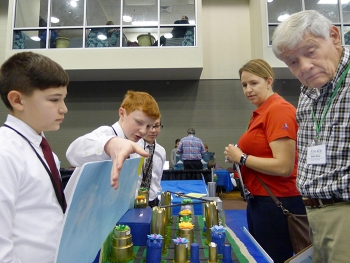 From left, Seventh-graders Cody Goldschmidt, Aaron Arnold, and Alex Trippi from Kennedy Middle School in Aiken, South Carolina guide judges Marissa Reigel and Robert Wilson from the organization Citizens for Nuclear Technology Awareness through their mode