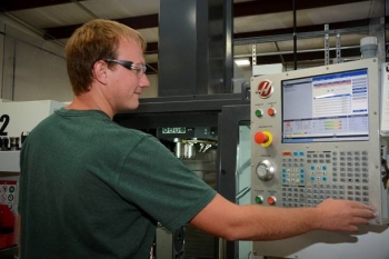 An employee with InSolves, a small, locally-owned business providing technical services and specialty manufactured products to Fluor-BWXT at EM's Portsmouth Site, operates a computer-controlled lathe in Piketon, Ohio.