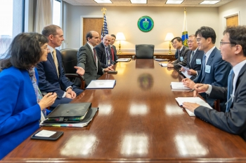 Ten representatives from DOE and Hyundai sit around a conference room table.