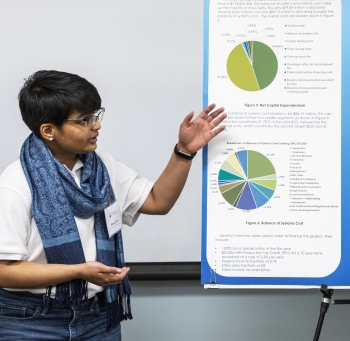 A young woman gestures toward a presentation poster.