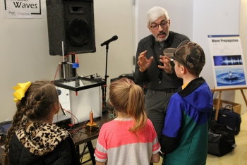Kevin Young, who works for Fluor Idaho partner North Wind Portage, teaches students about how waves form during Engineering Day at the Museum of Idaho.