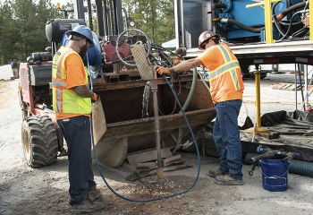 Injecting material containing iron filings into wells at the Savannah River Site is a multi-step process. A well is flushed with water, shown here, before workers add the iron filings to it.