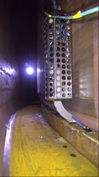 A wall crawler inserts an inspection sensor into a small air slot under the inner shell of a Hanford double-shell tank. In this waste storage tank, operators surveyed six air slots to obtain tank-bottom thickness readings at multiple locations.