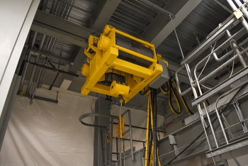 A 10-ton transfer hoist, located in the Hanford Site's Low-Activity Waste Facility, is a key component in moving containers filled with treated tank waste. During operations, the remotely operated hoist will function behind a shield door.