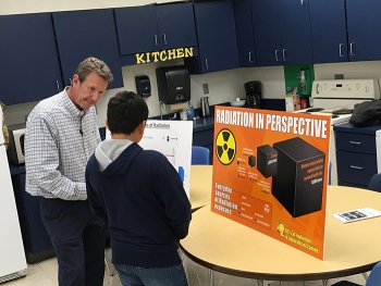 Joe Biggerstaff, a radiological protection integration and technical manager with UCOR, provides information about the sources of radiation to an attendee at the STEM event.