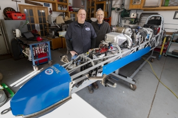 Sandia National Laboratories' Joel Wirth, left, and his father and labs retiree Jack Wirth stand next to their dismantled roadster in Joel Wirth's home garage. Between racing seasons, the car undergoes extensive repairs.