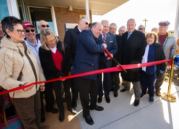 Holding an oversized pair of scissors, DOE Under Secretary for Science Paul Dabbar and Oak Ridge Mayor Warren Gooch cut a ceremonial ribbon to mark the grand opening of the K-25 History Center.