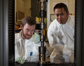 Aaron Bales, left, and Rob Panaro attach an extensometer to a tensile specimen. The extensometer gives an accurate measure of how much the specimen stretches during a tensile test.