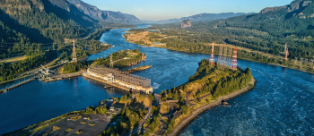 View of a hydropower facility and river at sunset.