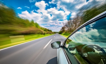 A car driving down a road. a clear sky with lots of cloud above.