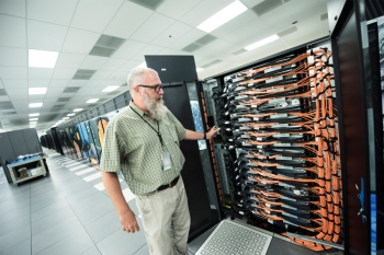 ALCF Director Michael E. Papka in the machine room that houses several supercomputing systems at Argonne National Laboratory, including Theta.