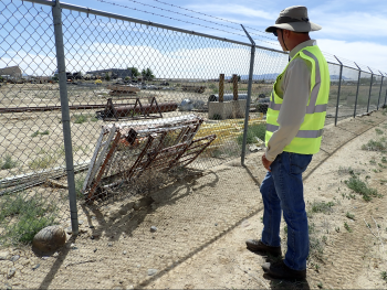 LM worker checks fence post on project at site.