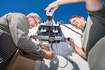 Two men set up a crawling robot against a clear blue sky.