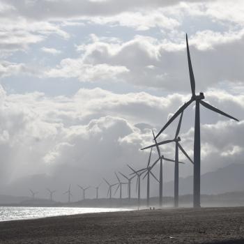 View of a wind farm along a foggy shoreline.