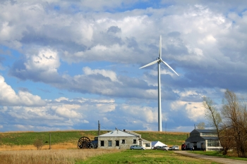 wind turbine on farmland against a cloudy but blue sky.