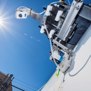 Photo of a crawling robot against a clear blue sky.