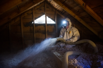 Weatherization worker insulating an attic.