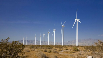 Wind turbines in an arid environment contrasted against a stark blue sky