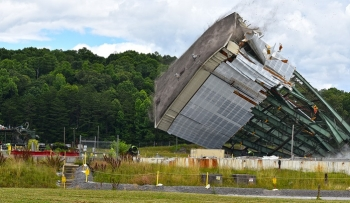 Crews use large winches to tear down a 180-foot tower of the Centrifuge Complex at Oak Ridge.