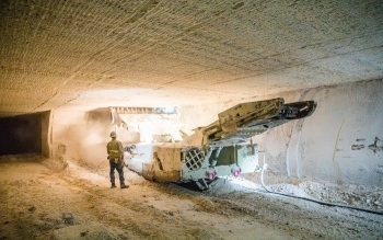 A worker operates a continuous mining machine 2,150 feet underground at the Waste Isolation Pilot Plant to create additional disposal rooms for transuranic waste. The rooms are carved out of 250-million-year-old bedded salt formation and measure 33 feet w