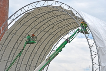 Crews are manually adding 12,000 square feet of fabric to the trusses to complete the cover for the protective tent at the Building 3026 demolition project at Oak Ridge.