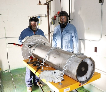 Isotek employees Shane Miles, left, and Ryan Souza stand behind a cutting tool used to help install new remote manipulators in hot cells at Oak Ridge.