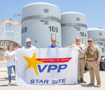 Nuclear Waste Partnership (NWP) President and Project Manager Sean Dunagan, center, helps unfurl the Voluntary Protection Program (VPP) Star site flag during a brief ceremony at the Waste Isolation Pilot Plant (WIPP) in late June.