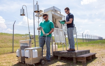 In this February 2020 photo, Savannah River Nuclear Solutions (SRNS) Scientist Jason Walker, left, inspects a new portable air monitoring station.