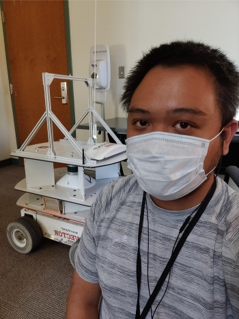 Pictured is Jeff Natividad and the Vector Waypoints robot. Natividad is working on a project to perfect an autonomous mobile robot for use in the Hanford tank farms.