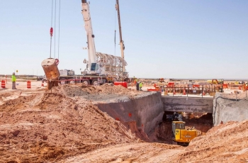 As a load of excavated dirt is dumped from the utility shaft, an excavator works on a sloped area that will hold the shaft's forced-air intake pipe, known as the plenum.