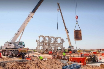 A bucket of excavated dirt is lifted out of the utility shaft at the Waste Isolation Pilot Plant site.