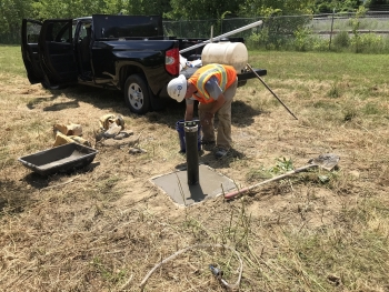A worker repairs a damaged monitoring well at the Colonie site.