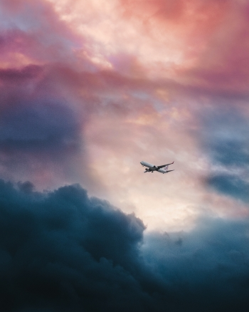 White plane flying through clouds.
